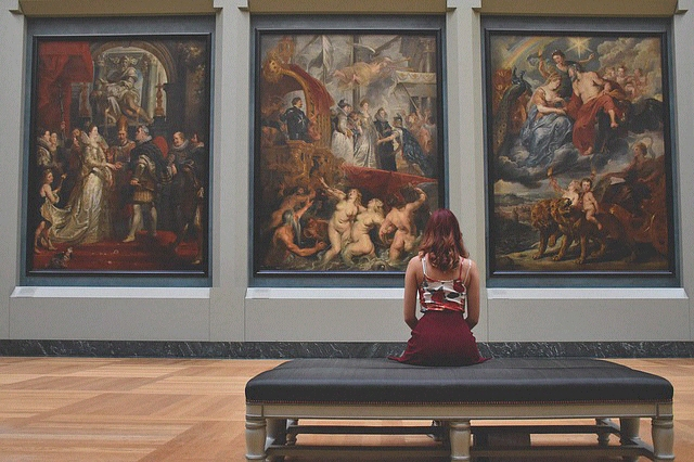 Girl sat on bench in art gallery