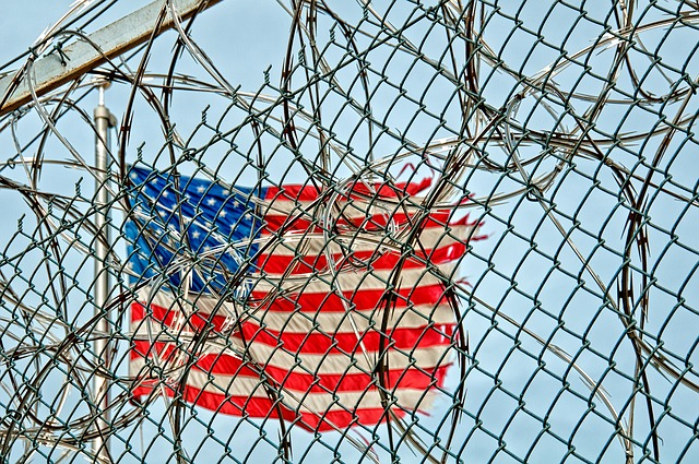 American flag and prison fence