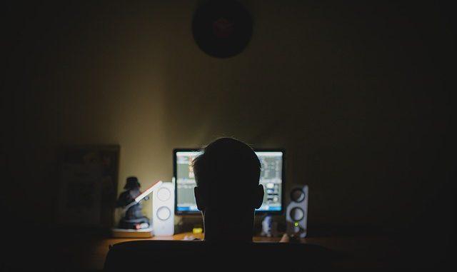 hacker sat at computer screen